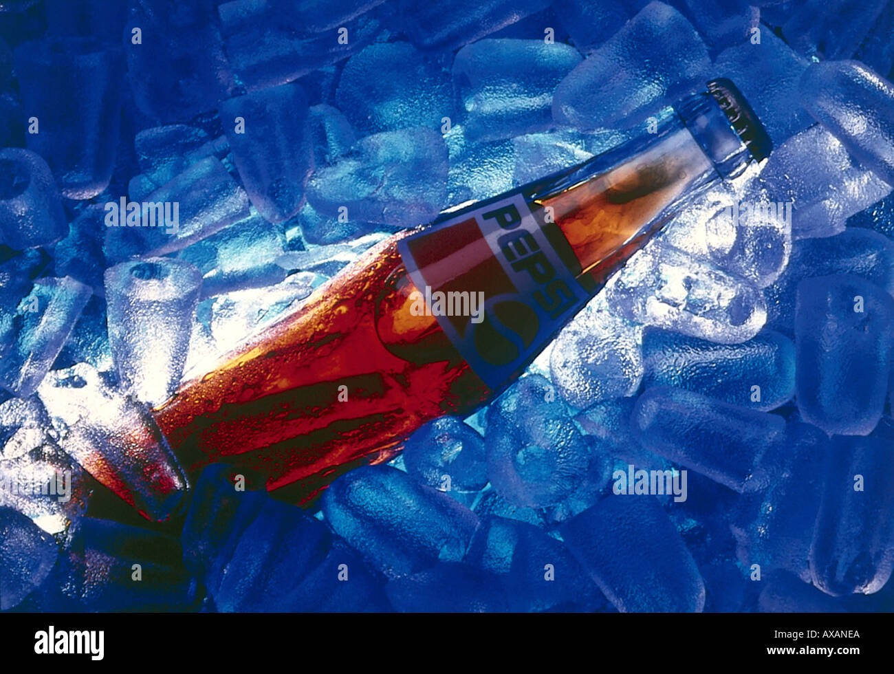 Icecold cola drink on bed of crystal clear icecubes in glass bottle of cold drink Pepsi cola and ice cubes Stock Photo