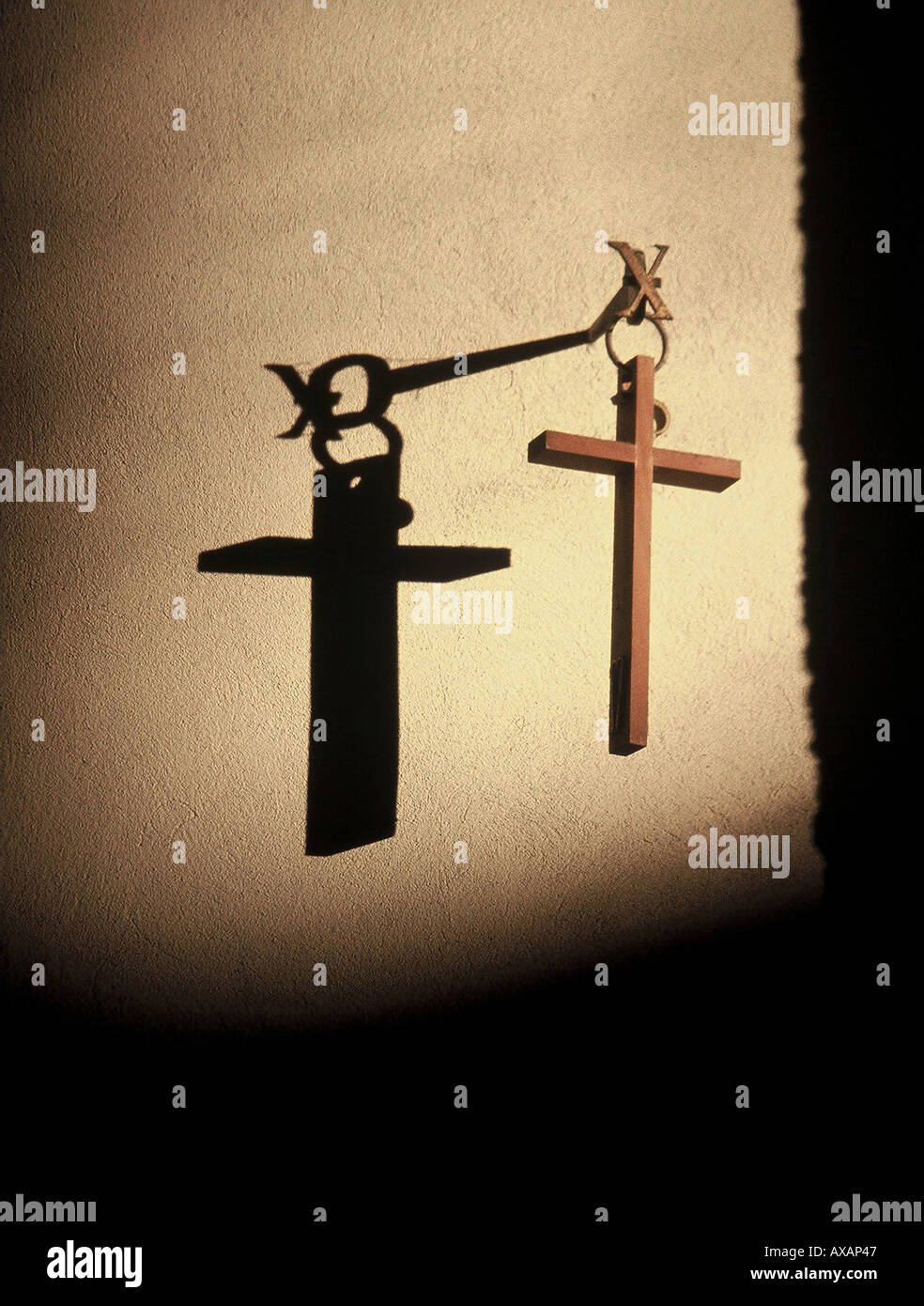 NMB74445 Conceptual and symbolic image of Lord God Jesus Christ and wooden cross and shadow on the wall - Stock Image