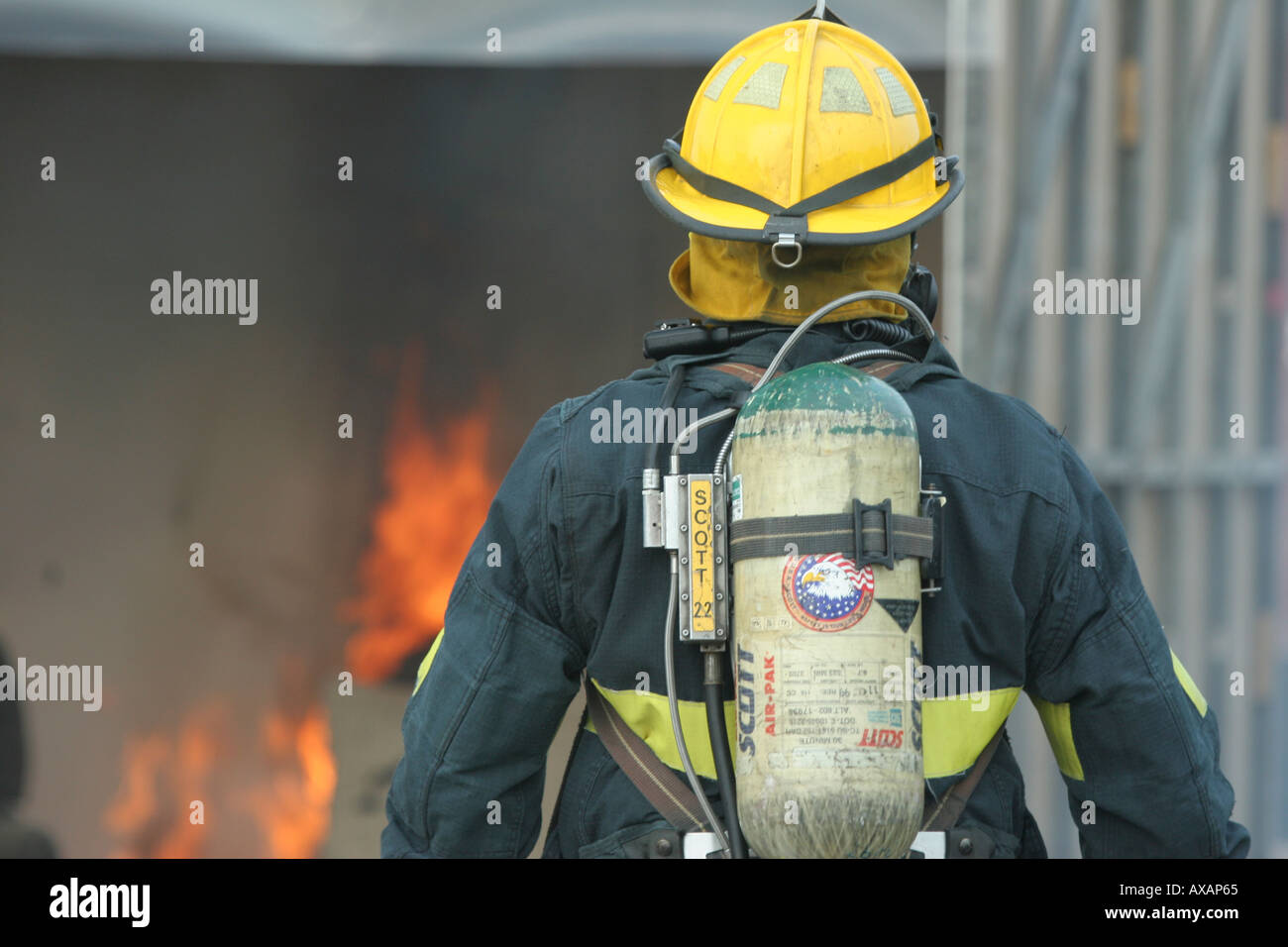 Fire fighter in yellow hat investigating flames in a container Stock Photo