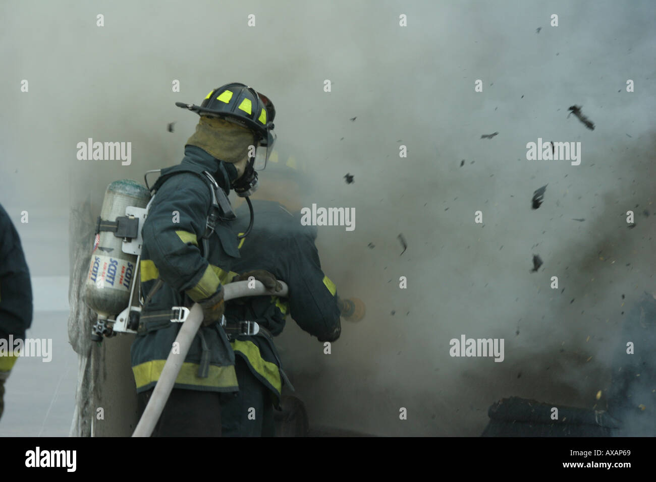 Fire fighters putting out fire in container with debris flying Stock Photo
