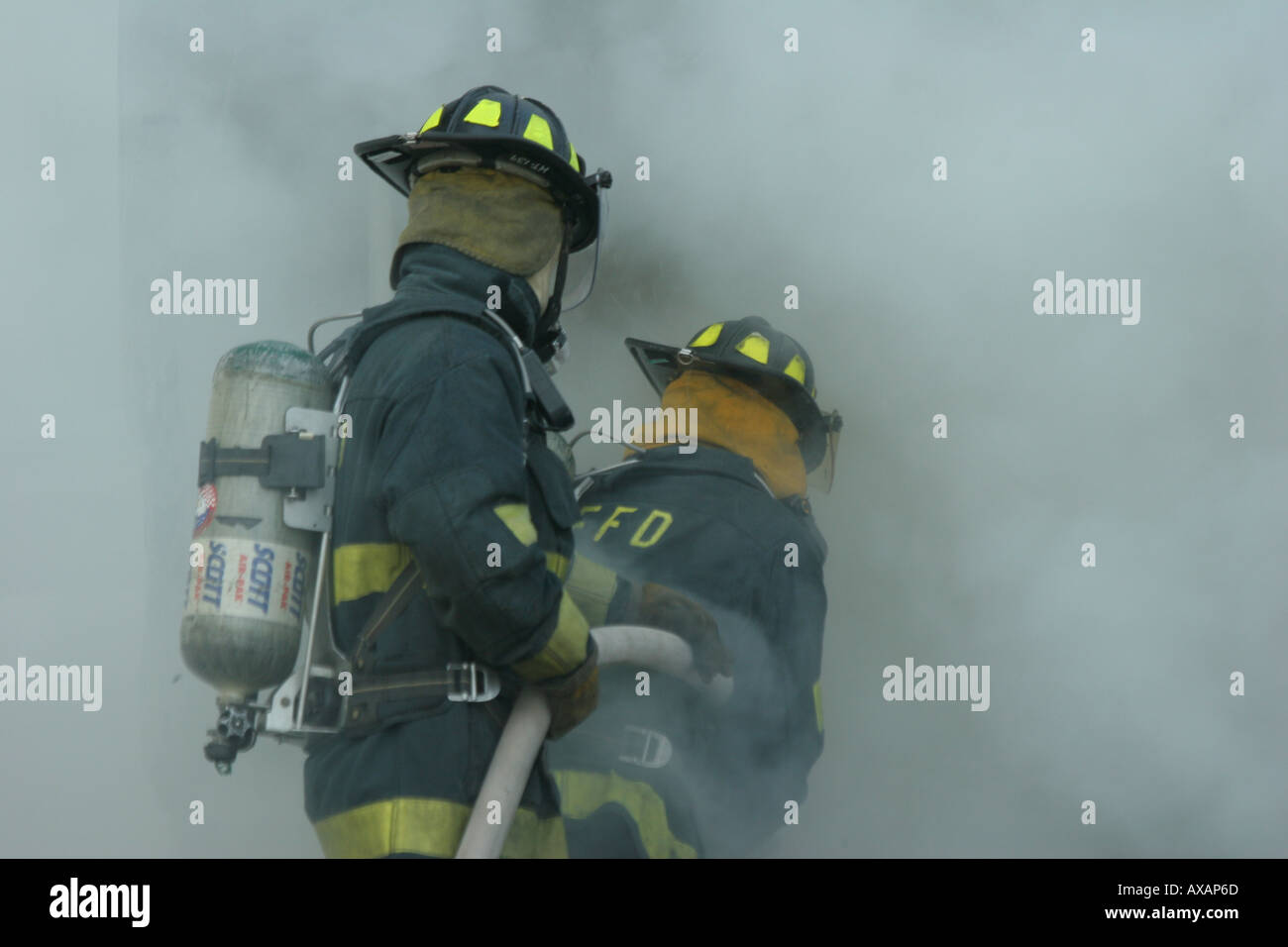 Fire fighters putting out fire in container Stock Photo