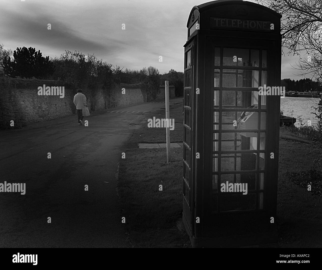 old red phone booth by a lake in uk - Stock Image