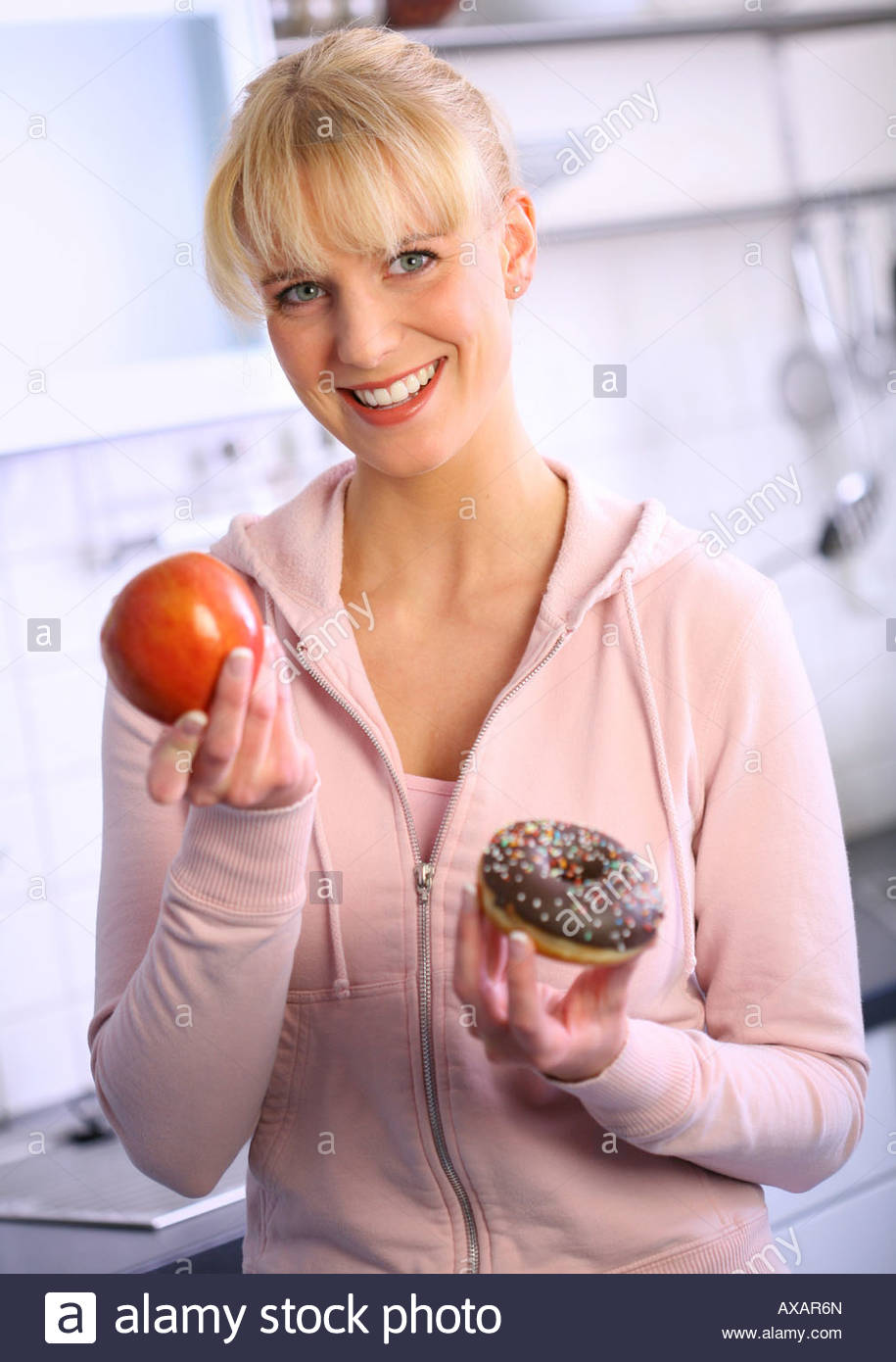 woman eating a snack holding an red apple and a donut in her hand - Stock Image