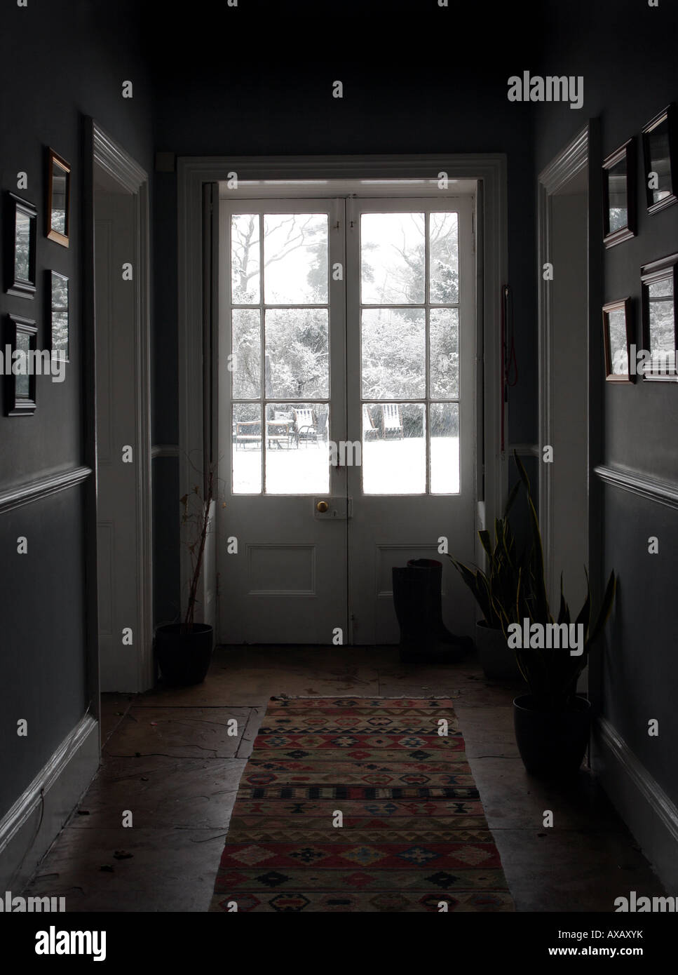 View down Georgian hallway to reveal it is snowing hard outside - Stock Image