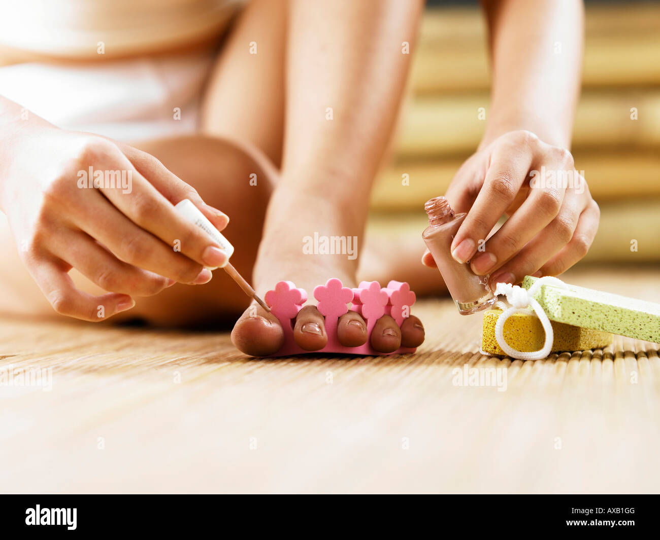Close Ups Of Toes Of A Young Asian Woman Applying Nail Polish On Her