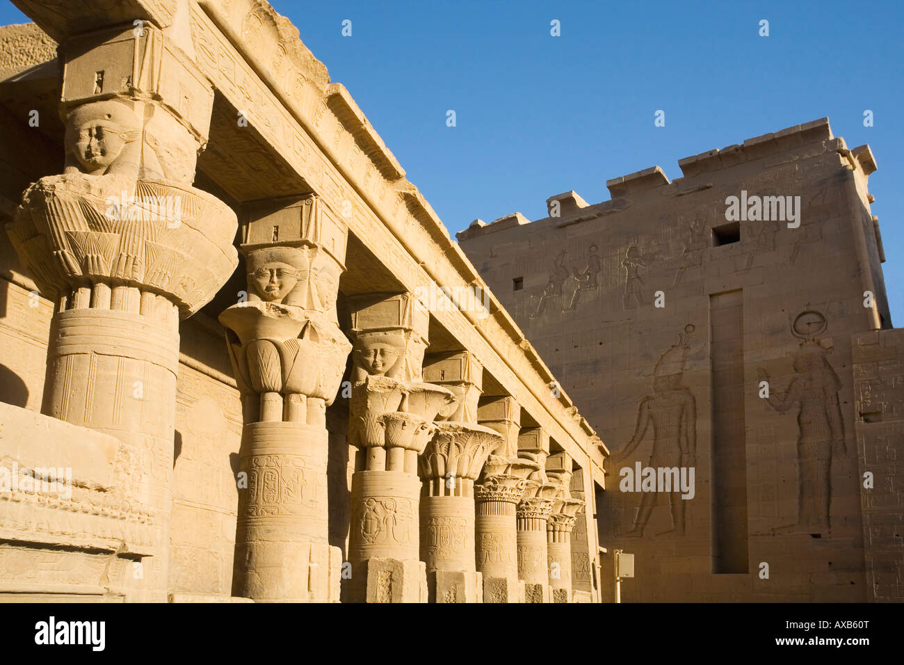 Mammisi and Second Pylon with papyriform capitals and face of Hathor with cow's ears  in the Temple of Isis - Stock Image