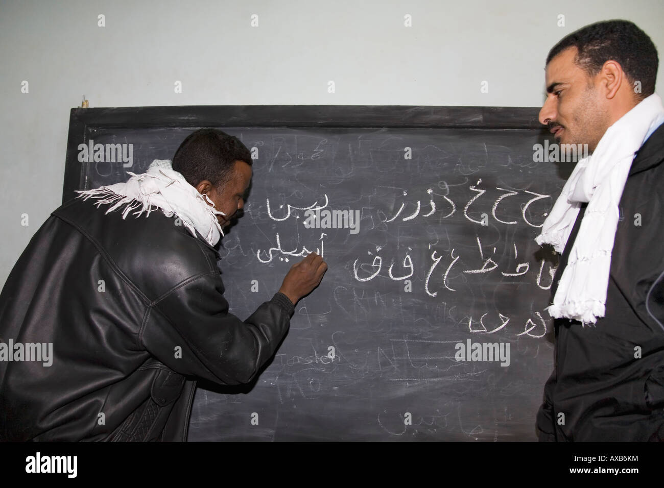 Egyptian teachers teach arabic writing on blackboard in classroom in Nubian village near Aswan Nubia Egypt North - Stock Image