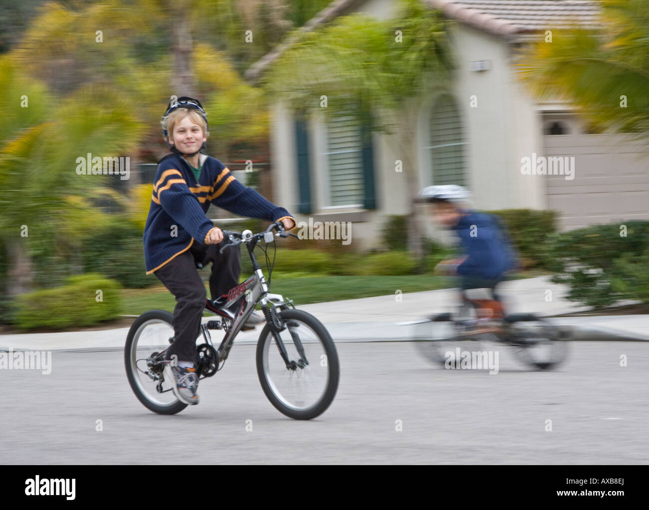 young buy riding a bike blurred shot - Stock Image