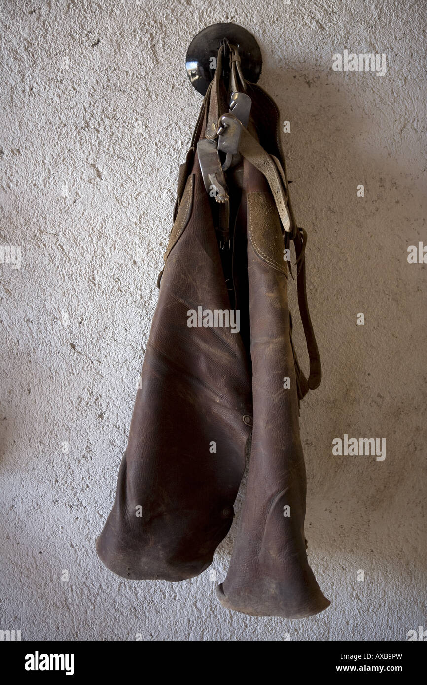 Carichi Mexico leather chaps and spurs hanged in a ranch stable - Stock Image