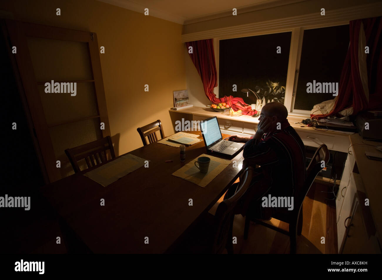 Man forties on the internet at home in a dark room - Stock Image