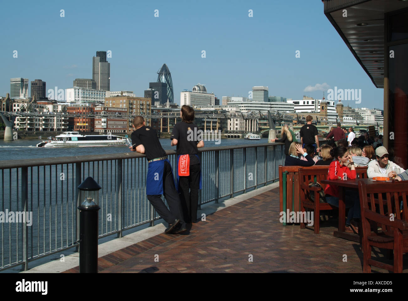 London riverside pub with customers at outdoor tables with staff leaning on railings with view of city skyline river traffic - Stock Image