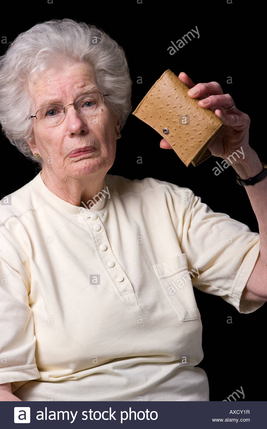 An old woman holding up an empty purse. - Stock Image