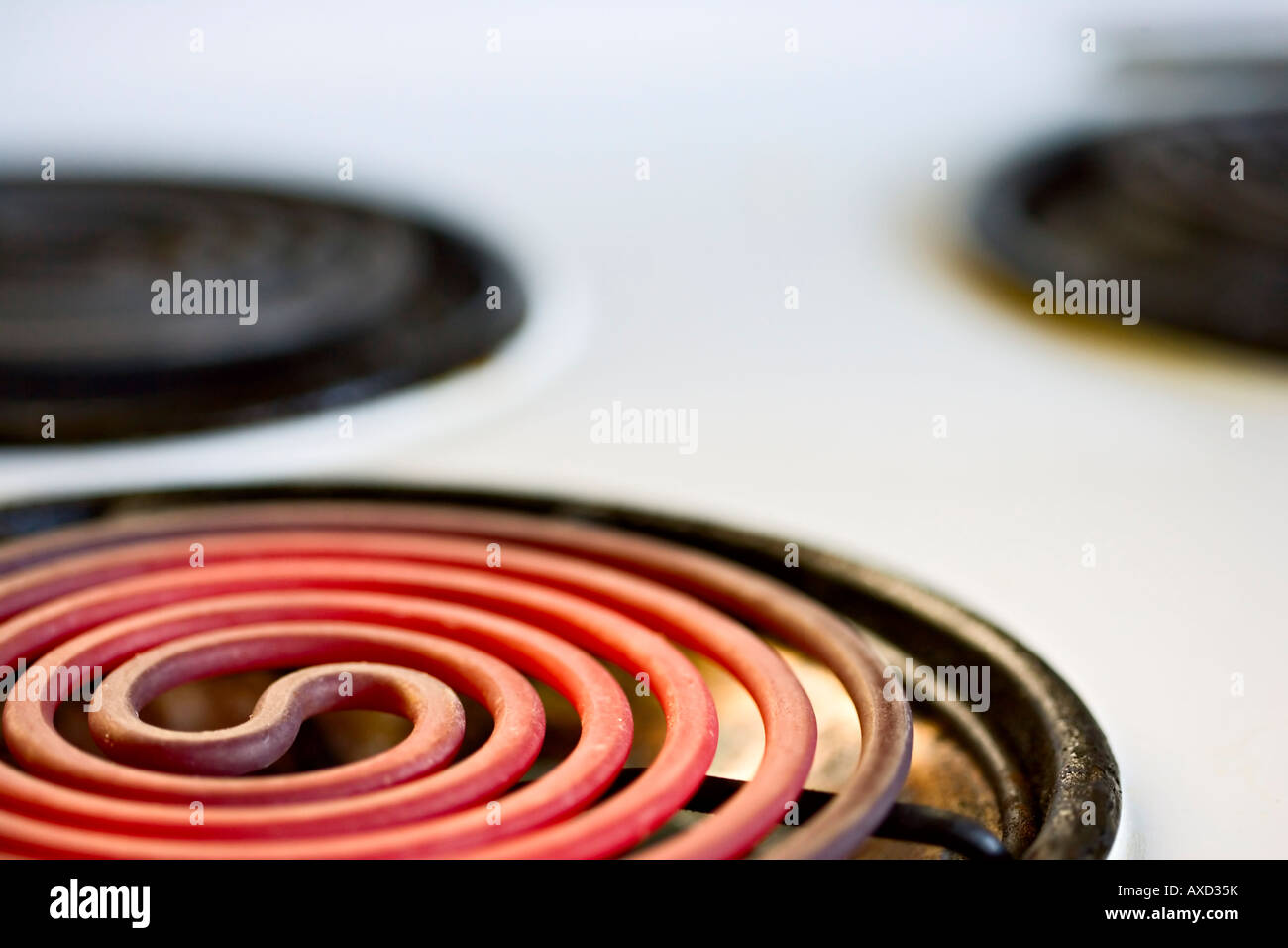 Old fashioned electric cooker hob glows red hot - Stock Image