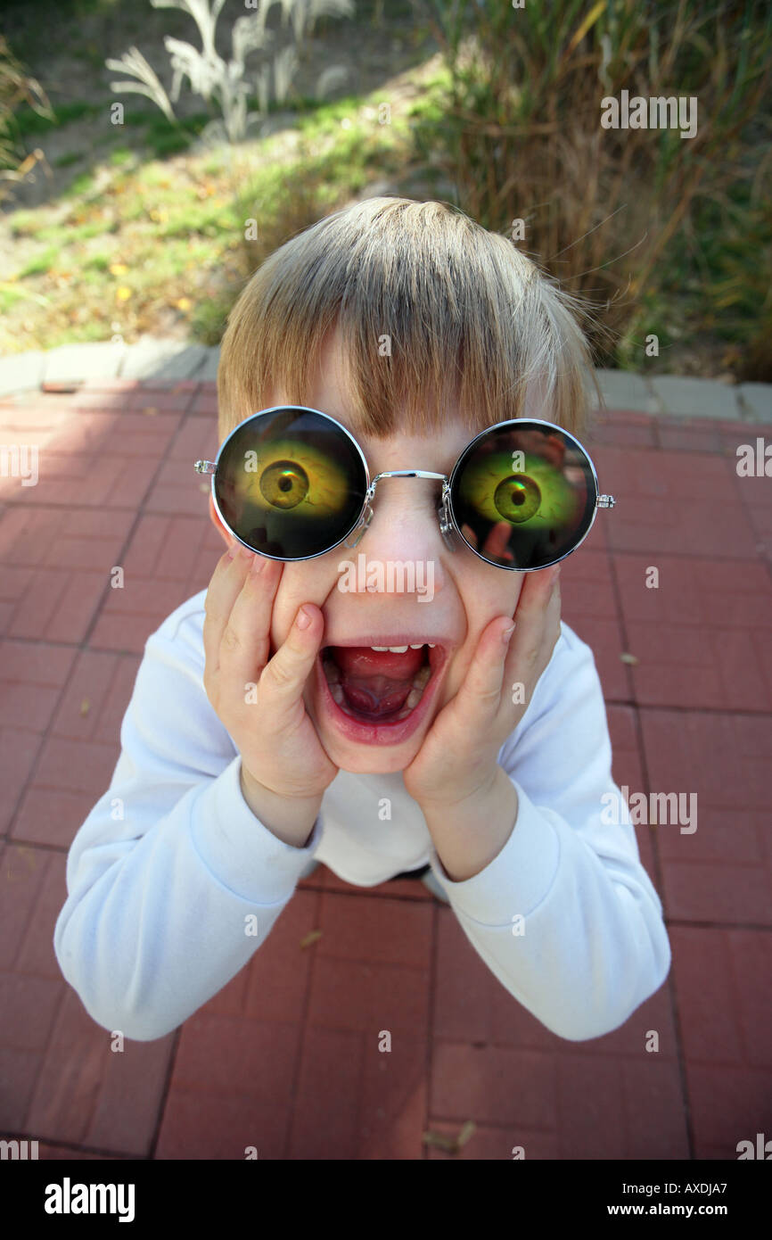 Stock photo of a child wearing holographic glasses with eyes. Silly, funny humor and surprise concepts - Stock Image