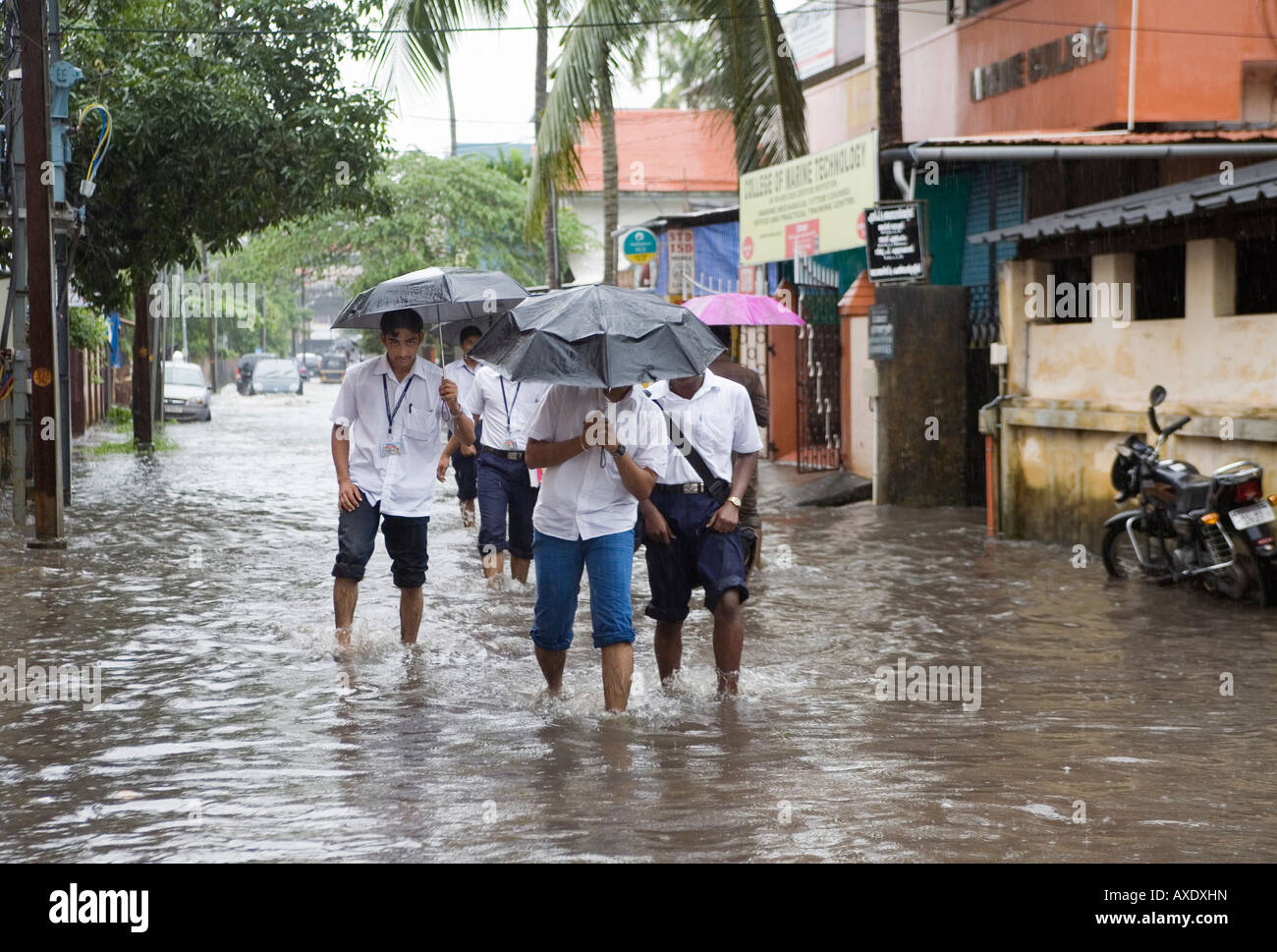 Young Indian schoolboys wading to school through flooded roads after monsoon showers Ernakulam Kerala South India - Stock Image