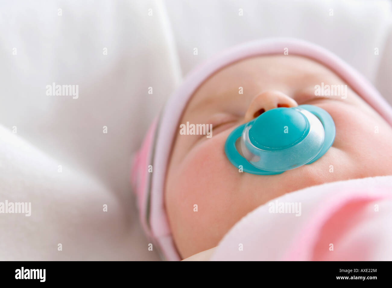 Baby boy (6-9 months) sleeping with pacifer, close-up - Stock Image