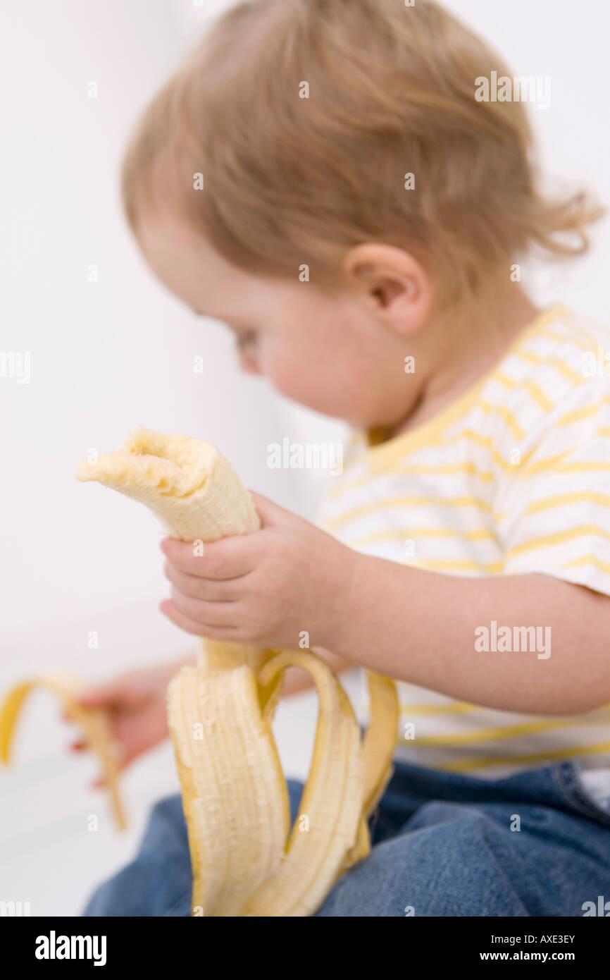 Baby girl (2-3) peeling a banana - Stock Image