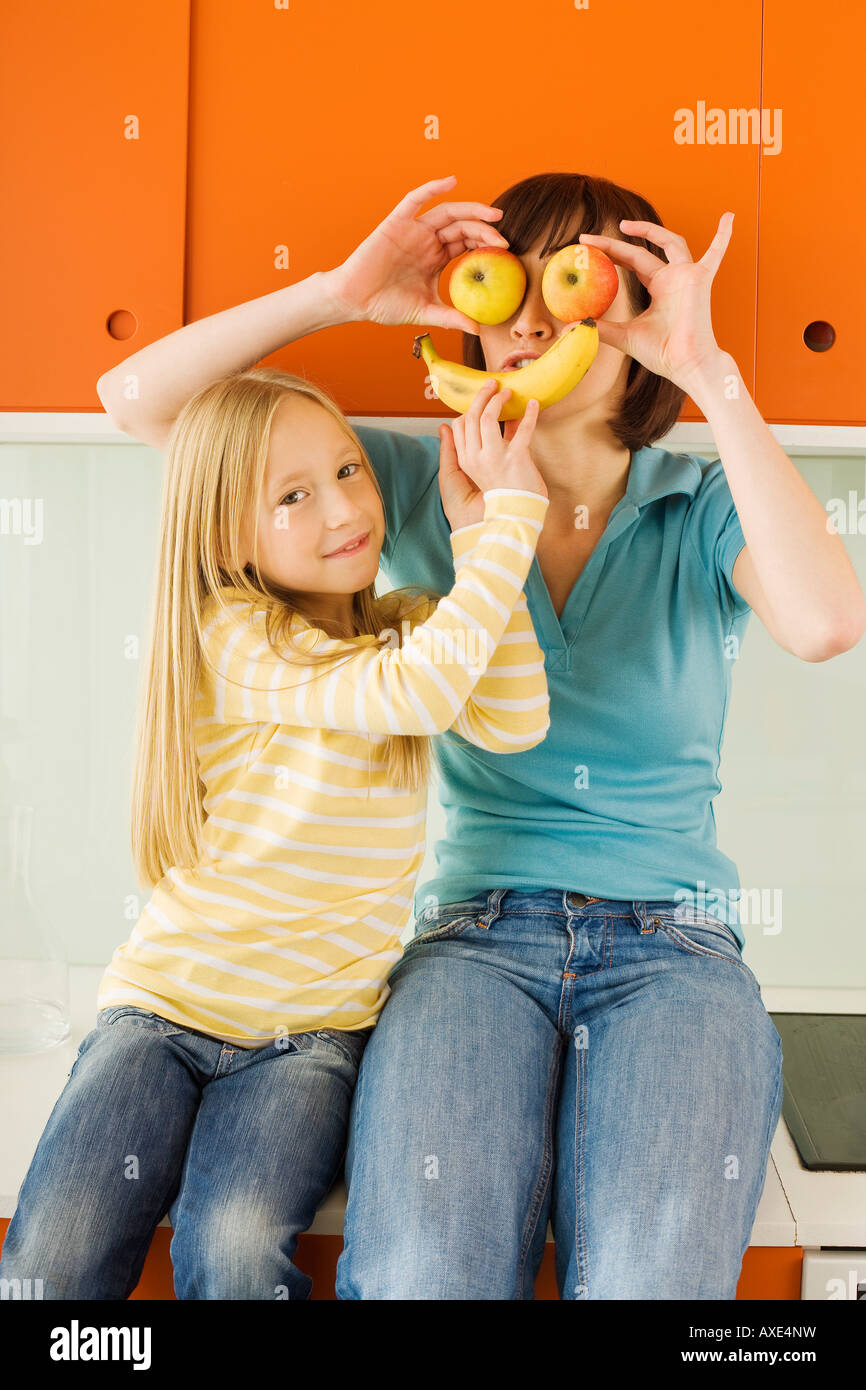 Mother and daughter (8-9) in the kitchen, mother holding apples in front of her eyes, - Stock Image