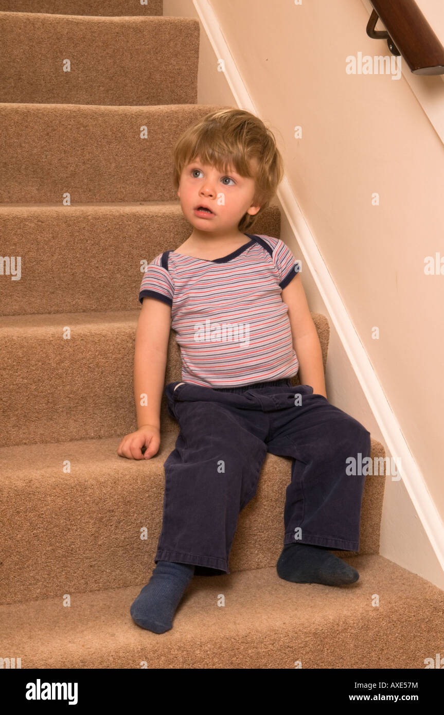 Two Year Old Boy Sitting At Bottom Of Stairs Perhaps As