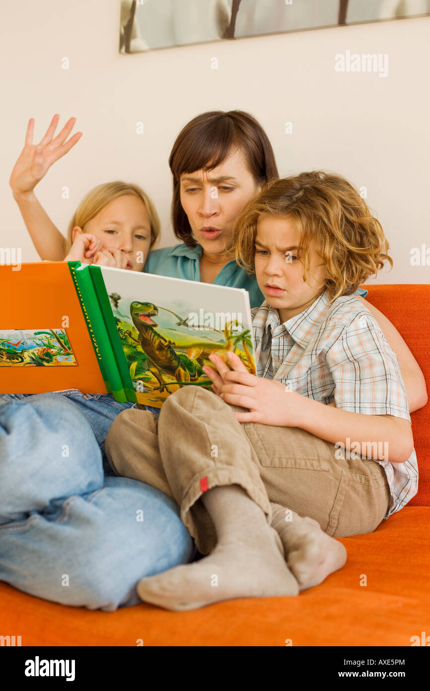 Mother reading story book to children - Stock Image