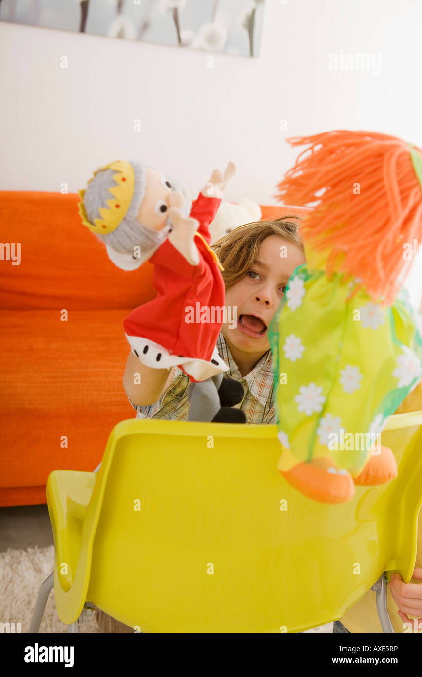 Boy (6-7) playing with glove puppets - Stock Image