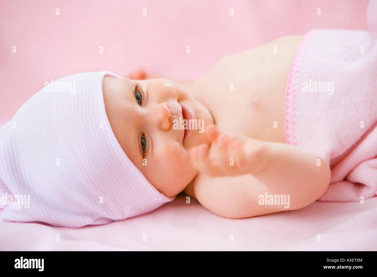 Baby girl (6-9 months) lying on back - Stock Image