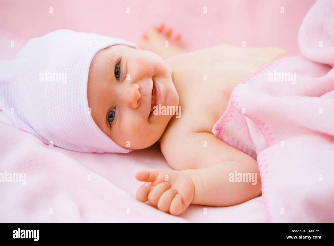 Baby girl (6-9 months) lying on back - Stock Image