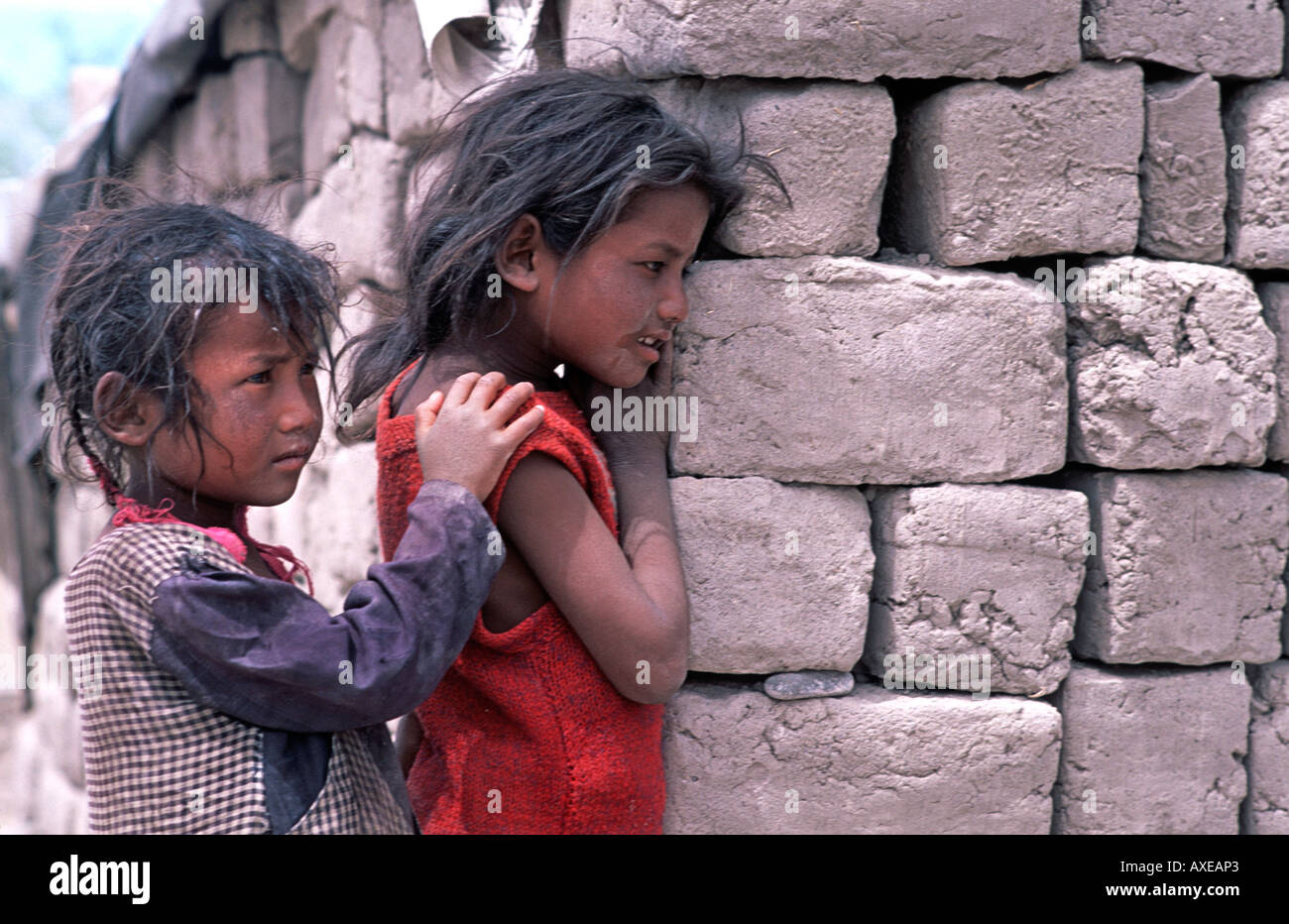 The daughters of Nepalese refugees peering around the adobe blocks of their makeshift home near Leh beside the Leh Stok junction - Stock Image