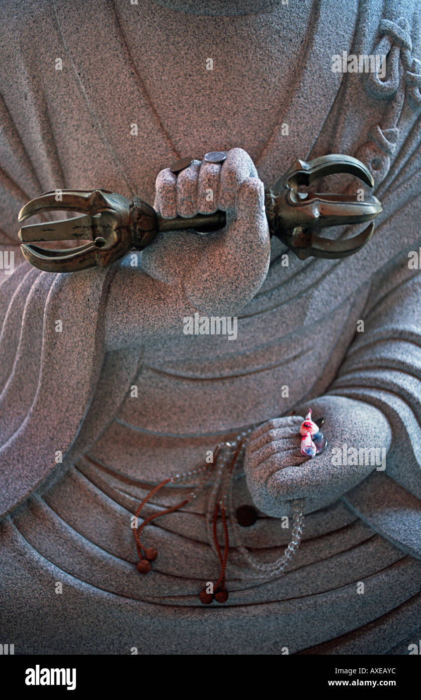 Close up of bead bracelets and coin donations on the hand of a budddha statue at Tsubosaka dera temple Nara prefecture Japan - Stock Image