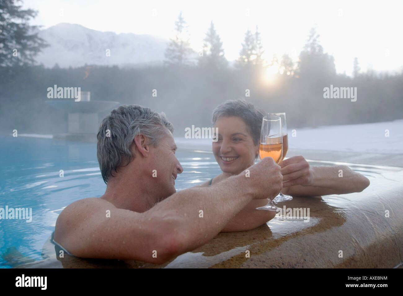 Mature couple with champagne in swimming pool, portrait - Stock Image