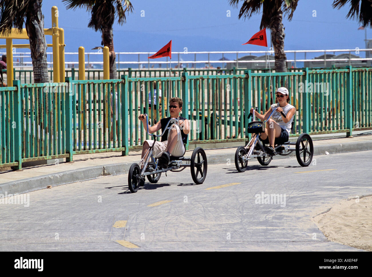 Tricycle riders on the cycle path at Venice Beach California - Stock Image
