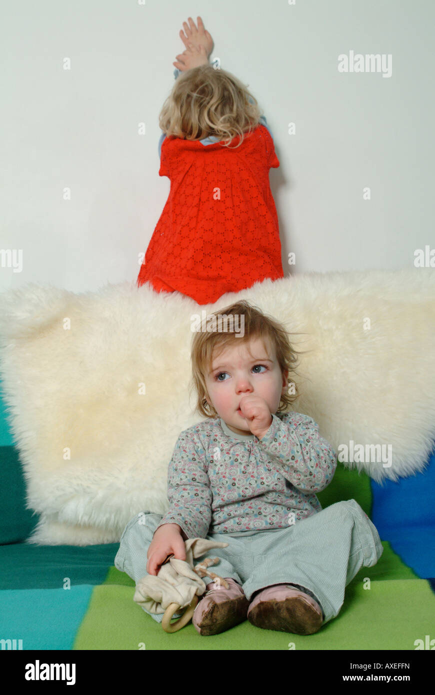 Two little girls sitting on the sofa, one sucking her thumb, the other sulking. - Stock Image