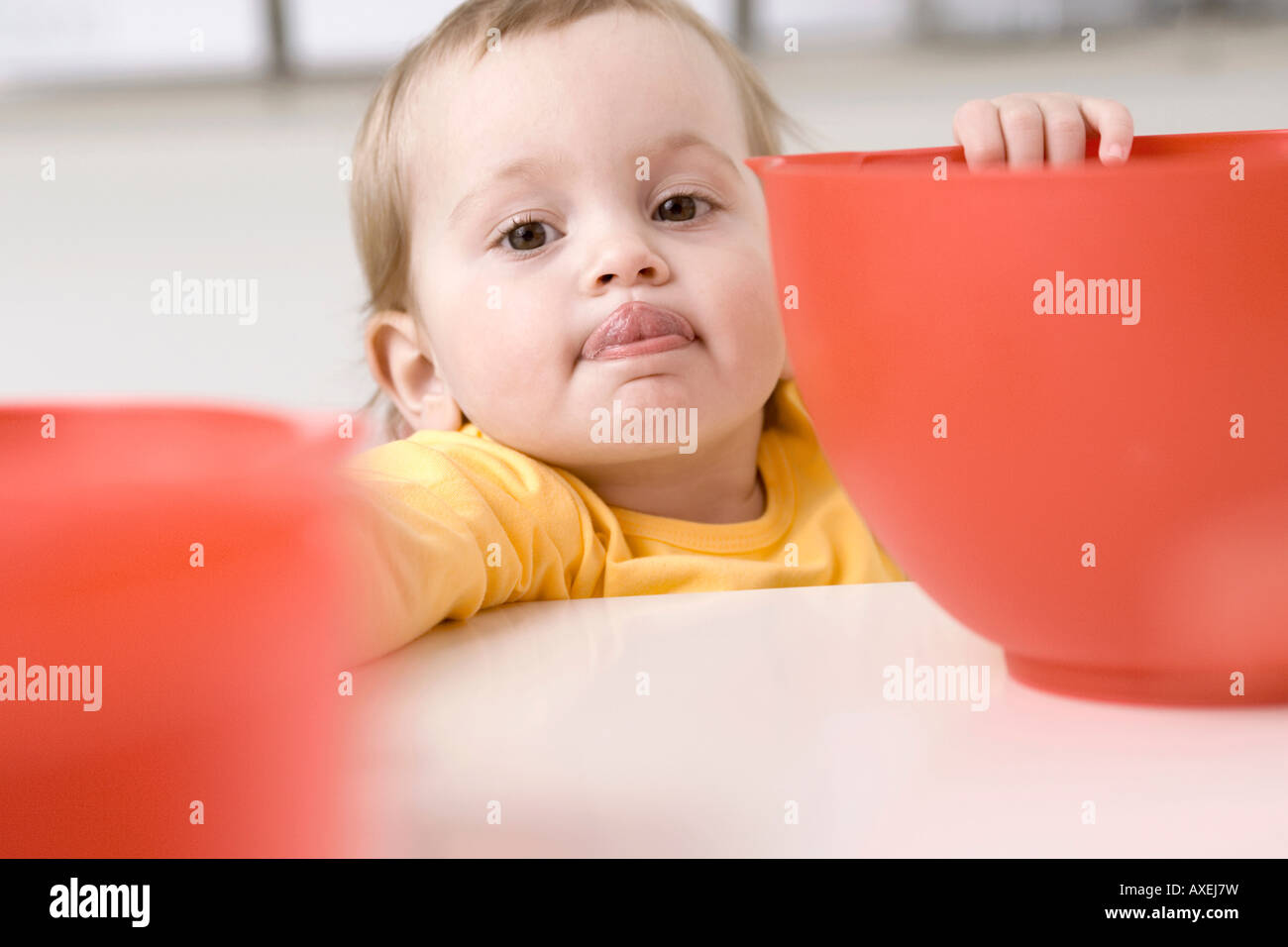 Baby girl (2-3) with bowl - Stock Image