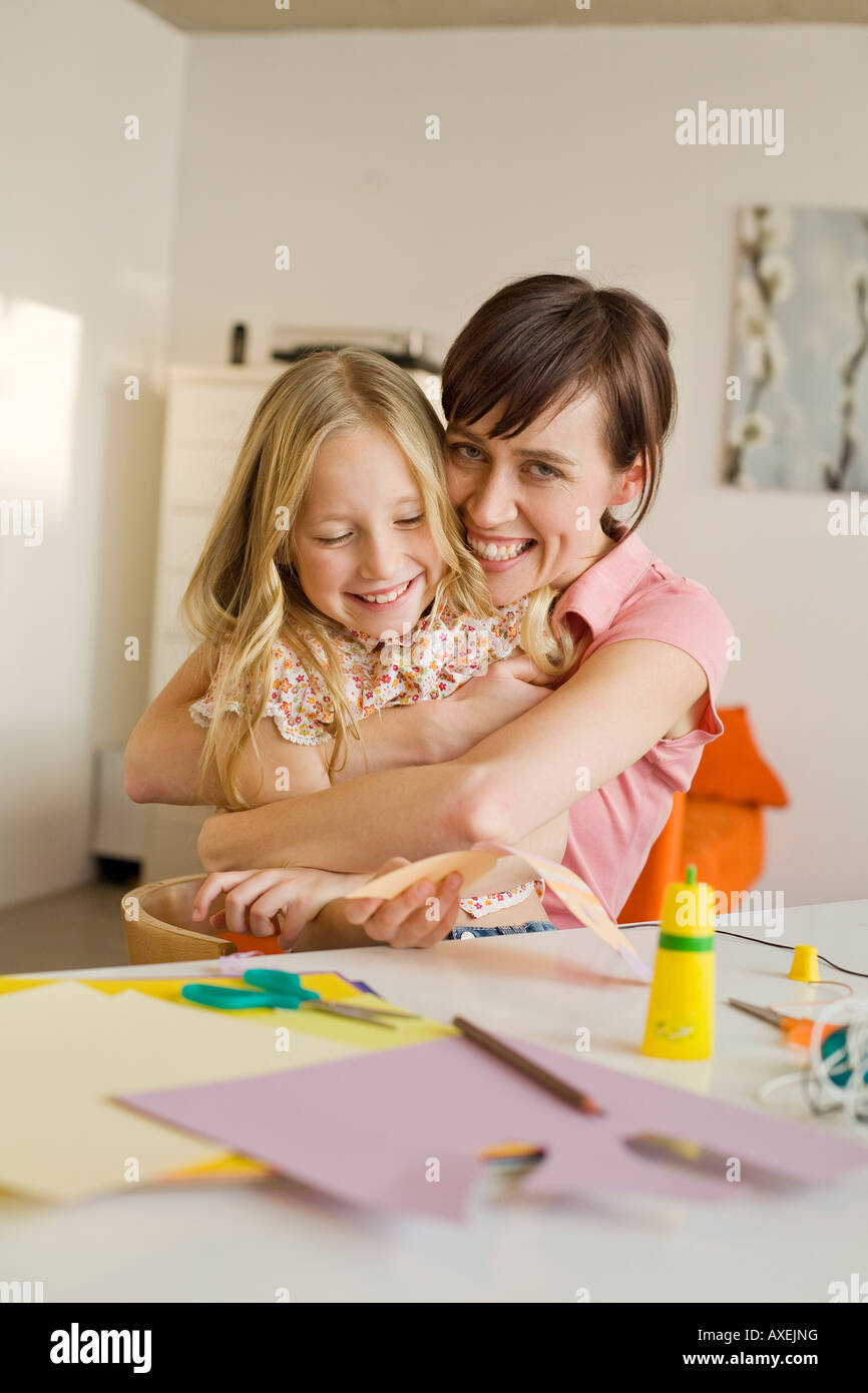 Mother embracing daughter (8-9), smiling, portrait - Stock Image