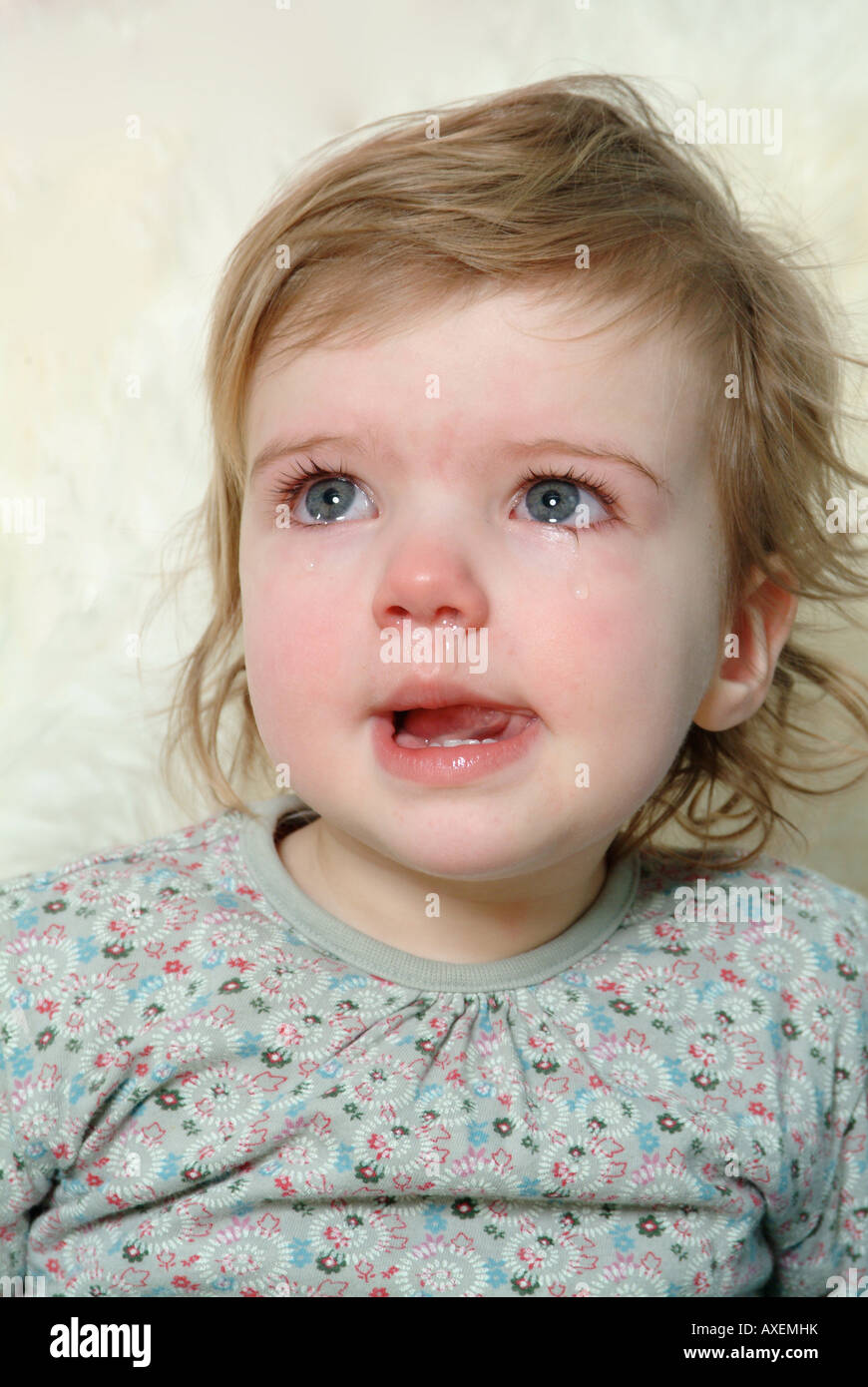 Little girl crying sitting against fur rug - Stock Image