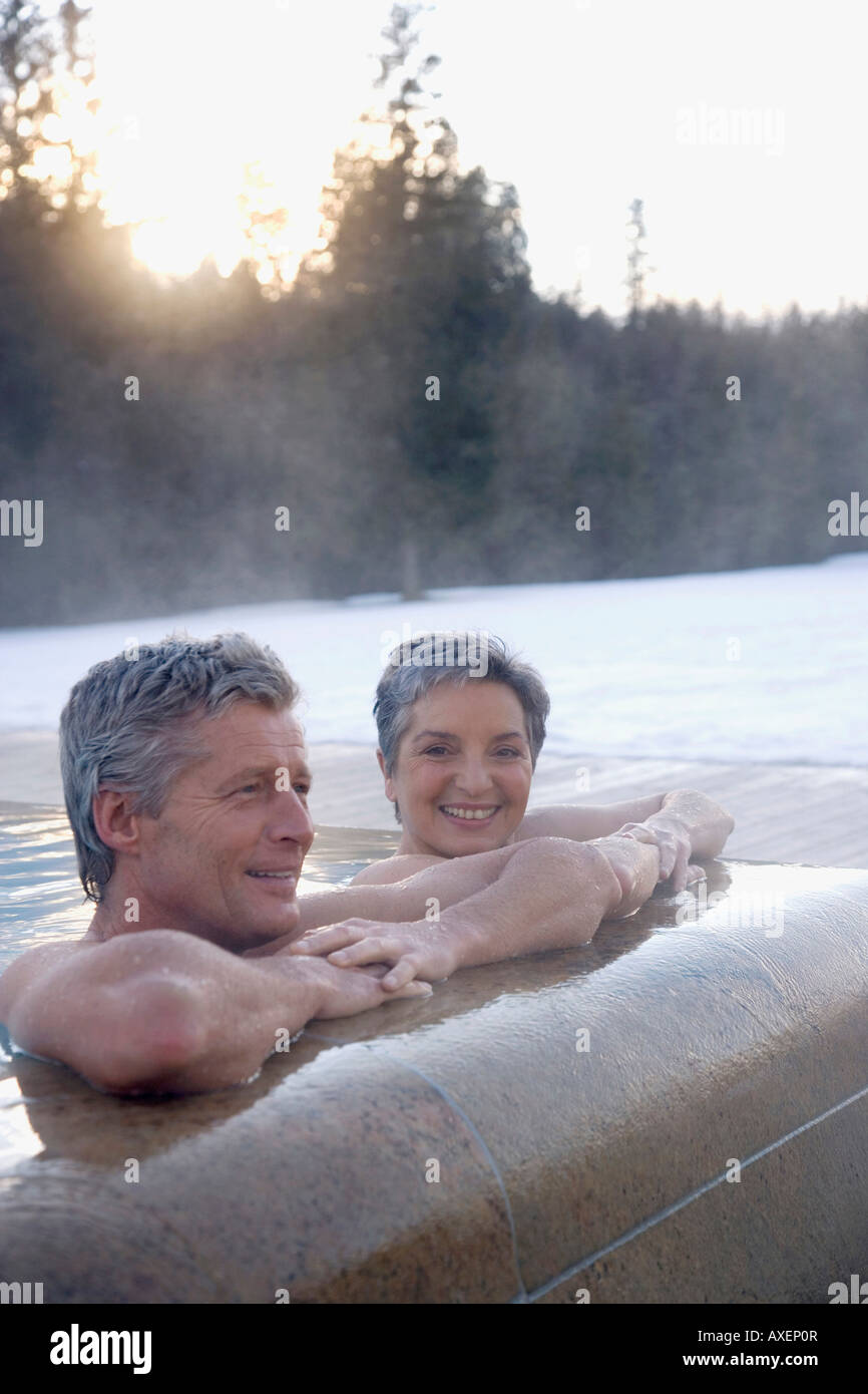 Mature couple relaxing in outdoor spa, portrait - Stock Image