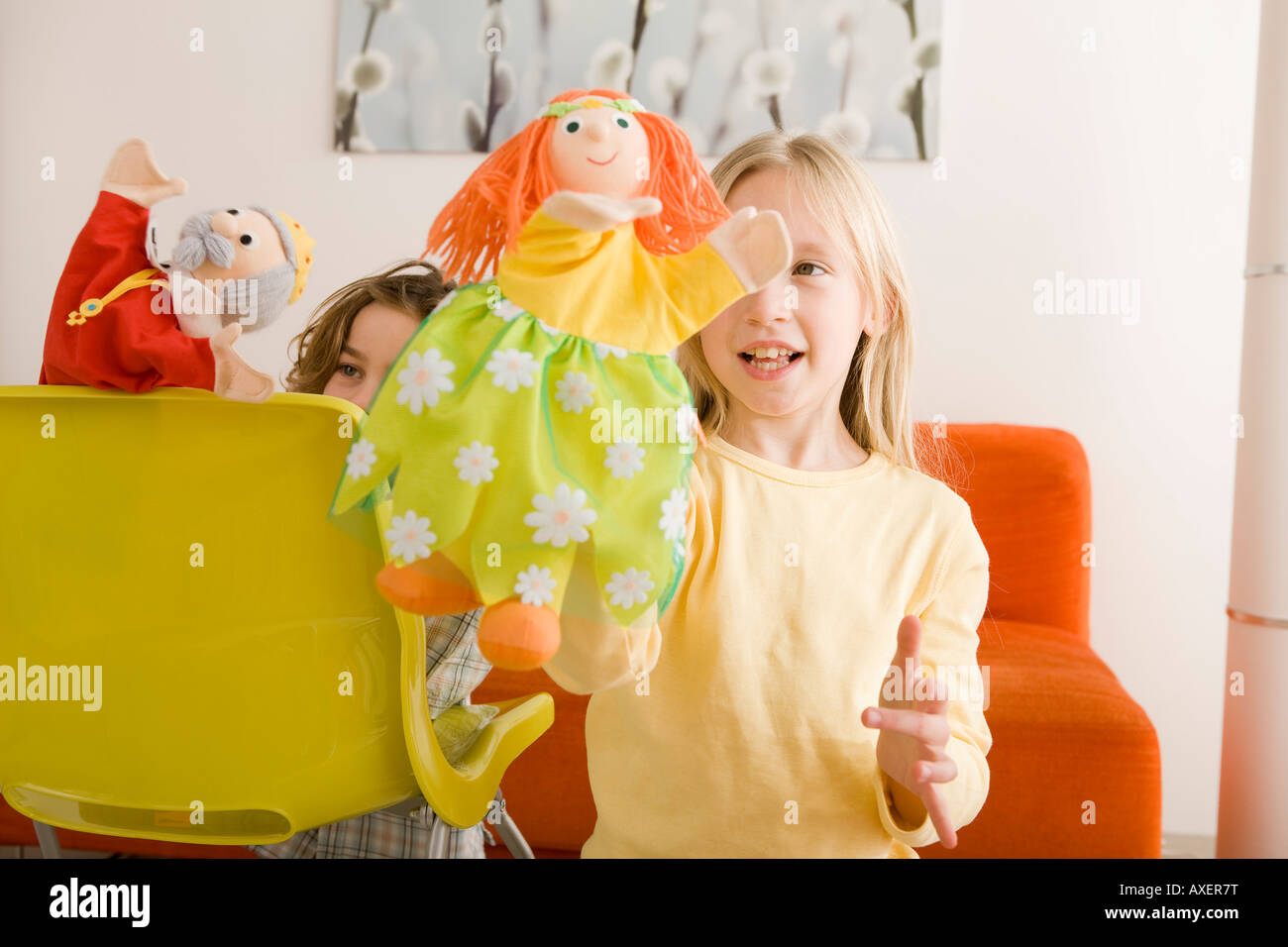 Girl (8-9) and boy (6-7) playing with glove puppets - Stock Image
