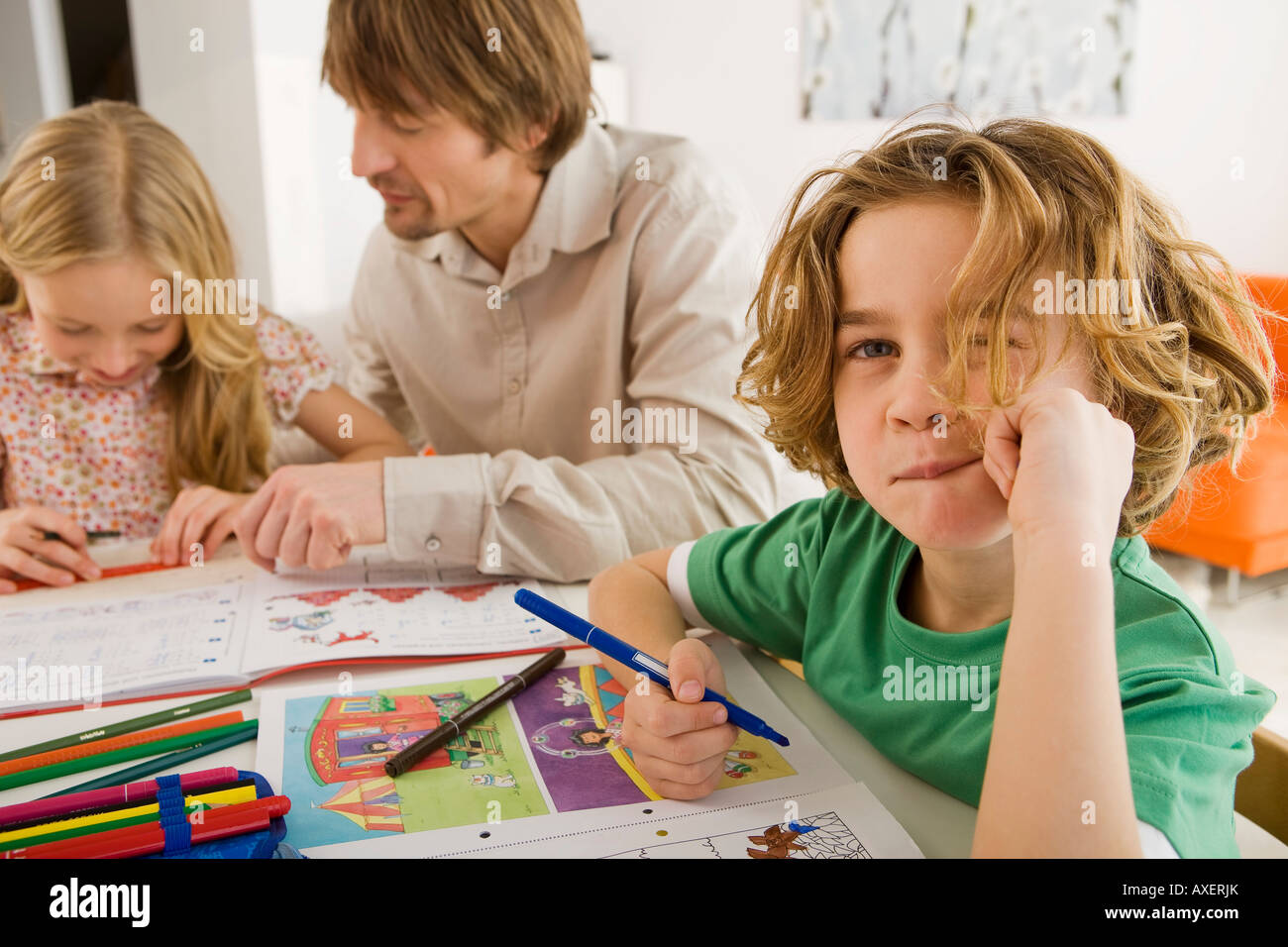 Father and children doing homework - Stock Image