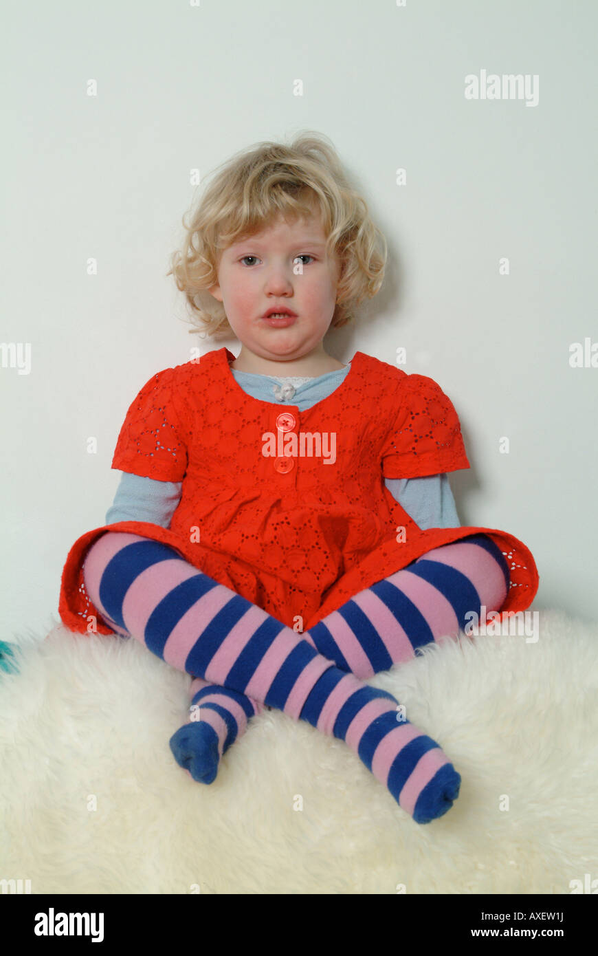 Little blond girl sitting crossed legged on fur rug, in red dress and stripy tights. - Stock Image