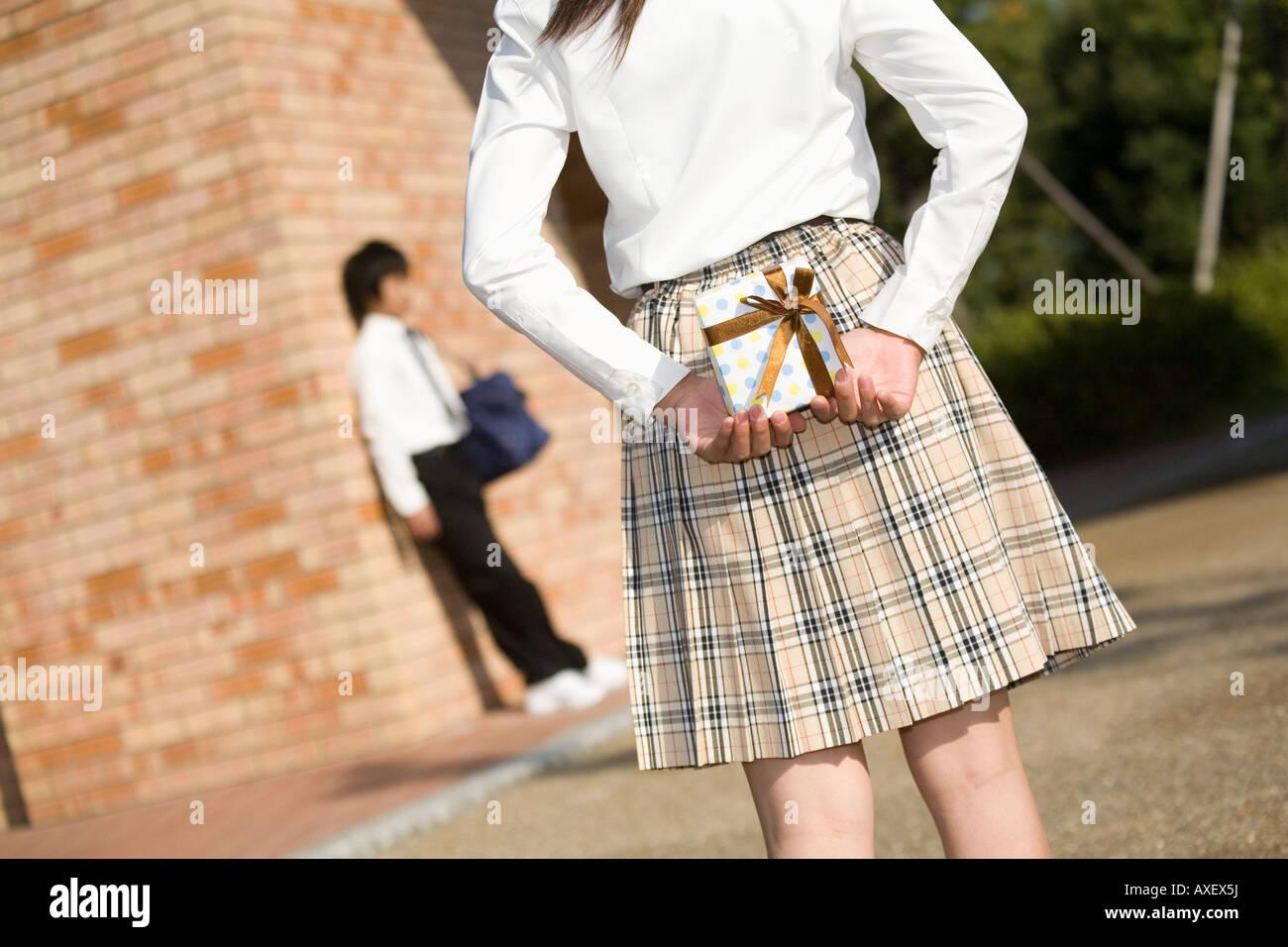 Schoolgirl holding gift - Stock Image