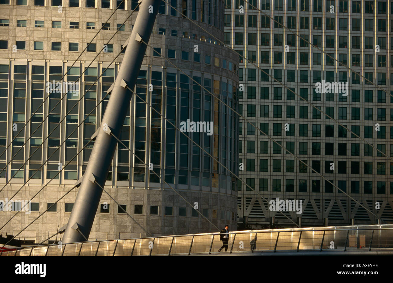 A lone person walks across a bridge in London's Docklands at Canary Wharf. - Stock Image