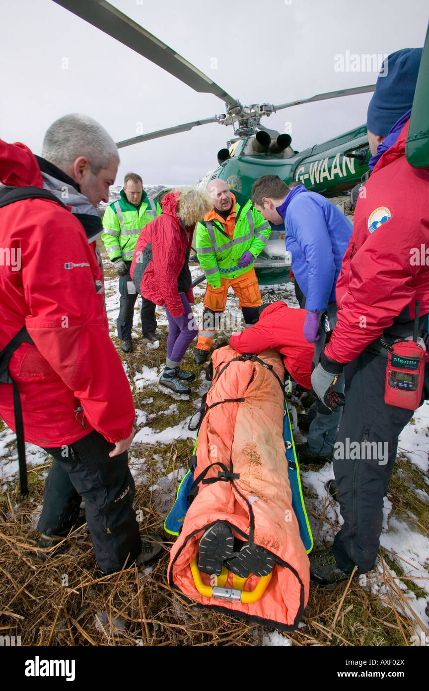 Members of Langdale Ambleside Mountain Rescue Team and an air ambulance doctor evacuate an injured walker - Stock Image