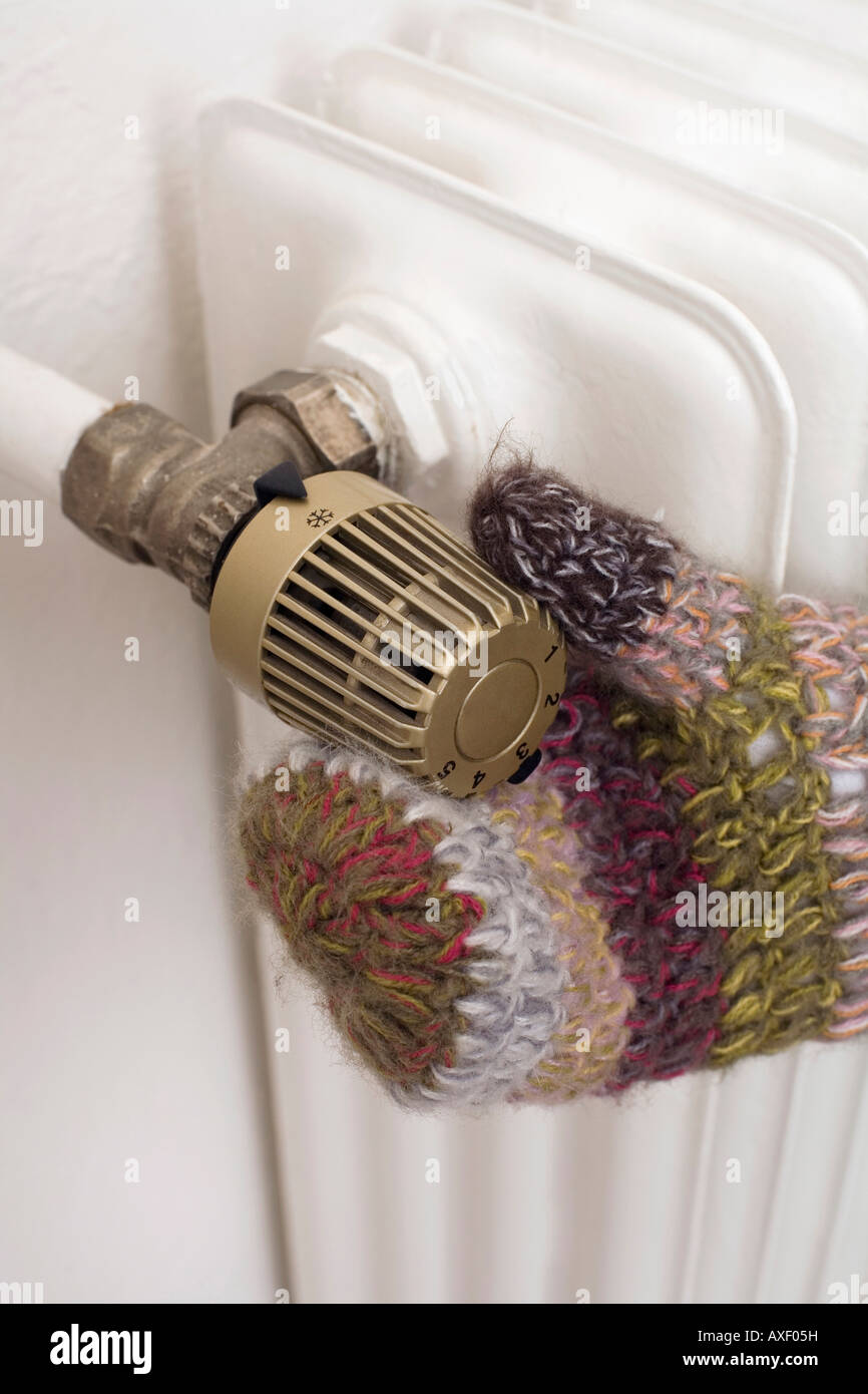 Hand on heating regulator - Stock Image