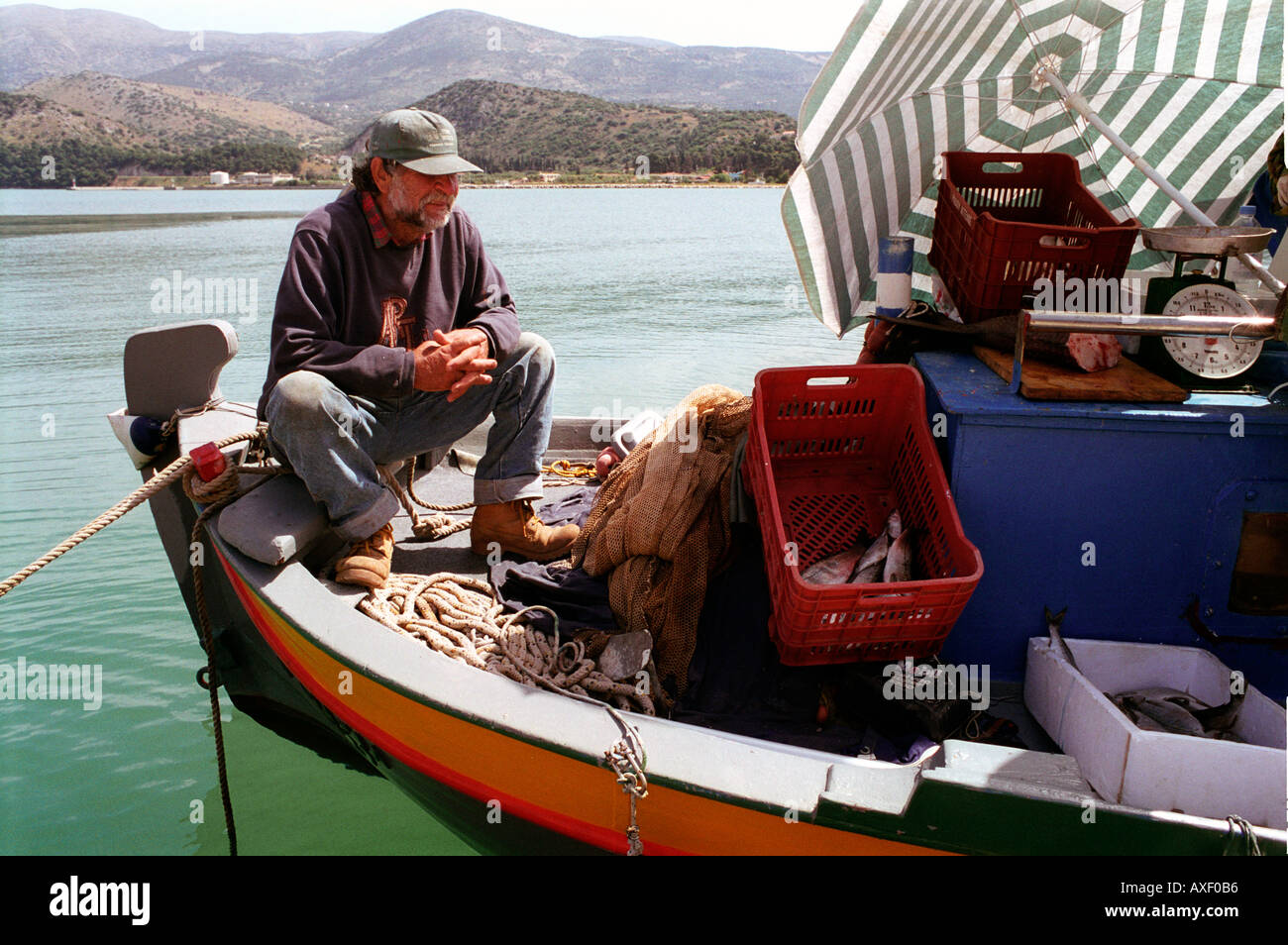 Fisherman going through cleaning out the days catch in harbour of Arastoli on Kefalonia Greek Island. - Stock Image