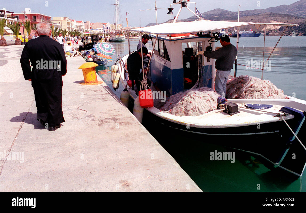 Fisherman going cleaning out the days catch as priest walks by in harbour of Arastoli on Kefalonia Greek Island. - Stock Image