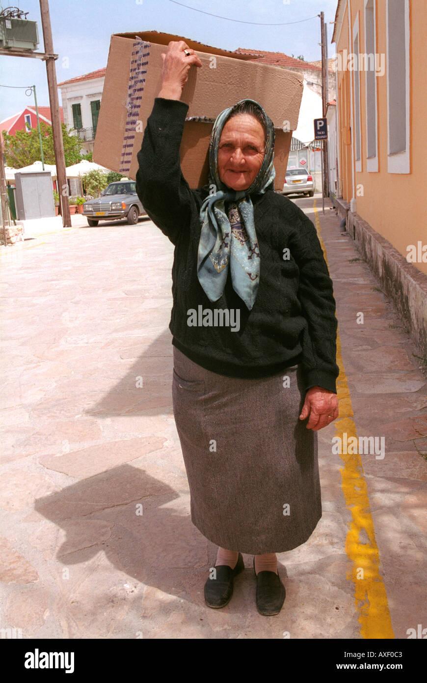 Elderly woman carrying box on her head through village street in  Sami on Kefalonia. - Stock Image