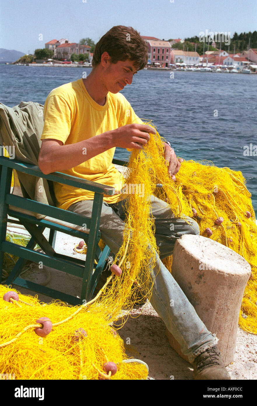 Fisherman fixing fishing nets at northern village of Fiscardo on Kefalonia an Ionian Island. - Stock Image