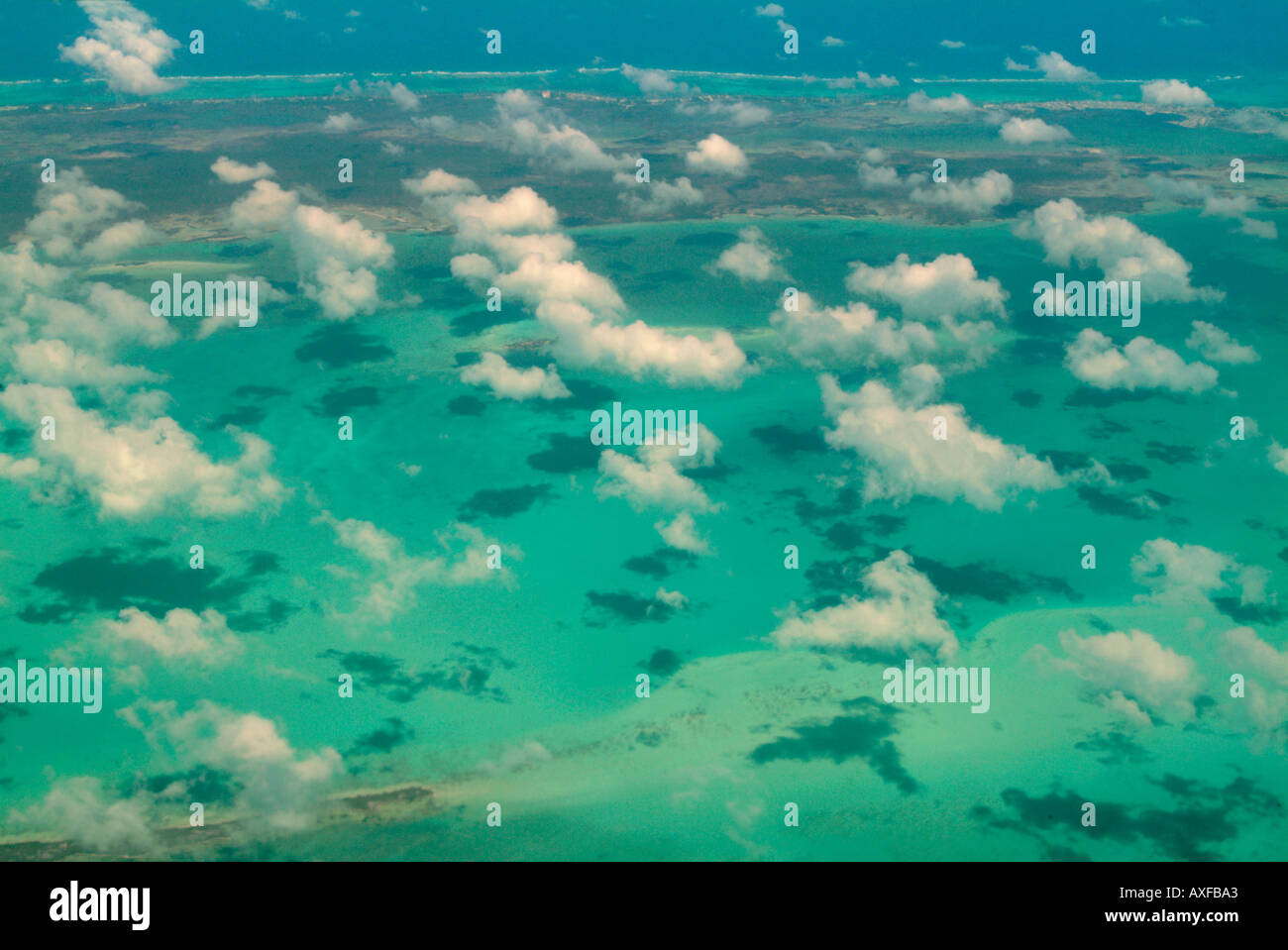 A birds eye view of a caribbean island and fringing reefs in this aerial shot. - Stock Image