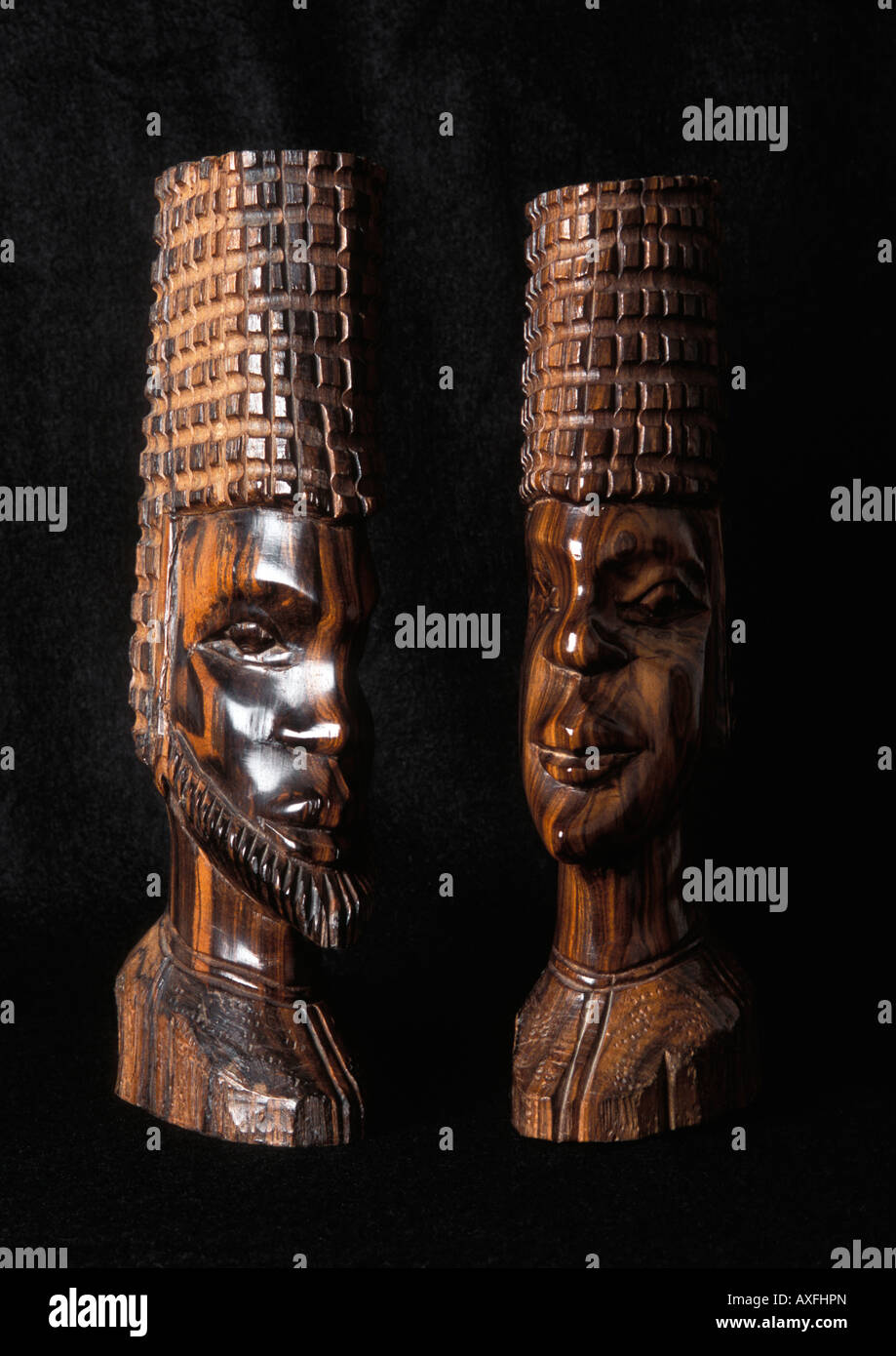Pair of Ghanaian wooden head busts on black background - Stock Image