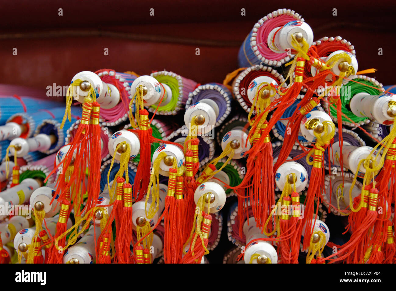 A row of closed Chinese silk umbrellas - Stock Image